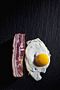 Fried hen's egg and bacon on slate - CSF025009