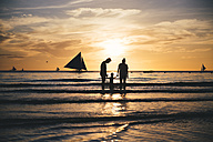 Philippines, Boracay, family with one child at seashore by sunset - GEM000129