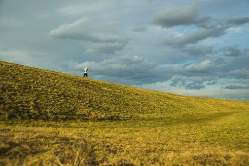 Germany, Mannheim, young man jogging in meadow - UUF003630