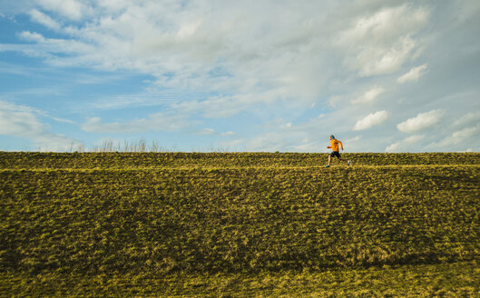 Germany, Mannheim, young man jogging in meadow - UUF003632
