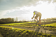 Germany, Mannheim, young man riding bicycle - UUF003634