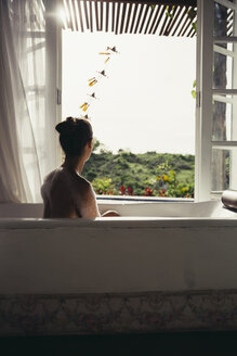 Woman relaxing in bathtub looking out of open window - MBEF001340