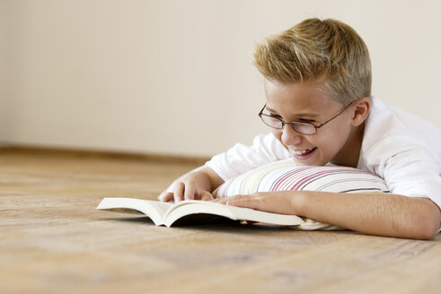 Smiling boy lying on wooden floor reading a book - LBF001094