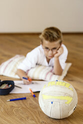 Boy doing homework on wooden floor with soccer ball lying in the foreground - LBF001092