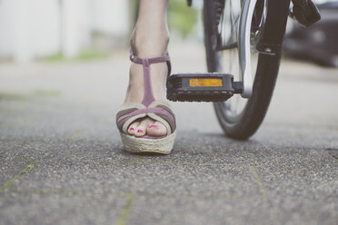 Close-up of woman with wedges on bicycle - CHPF000114