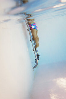 Underwater shot of toddler girl standing on boarding ladder in swimming pool - LS000059