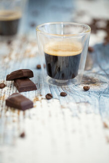 Glass cup of espresso, roasted coffee beans and dark chocolate on wood - LSF000014