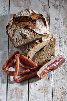 Loaf and slices of brown bread, bacon, sausages and knife - CSF025027