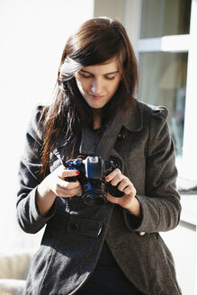 Young woman looking at her digital camera - LS000022