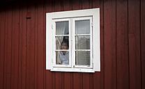 Norway, Lofoten, woman looking through window - MKFF000191
