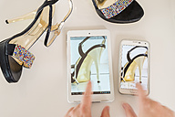 Woman using mini tablet and smartphone for comparing different offers of high heels - CSTF000894