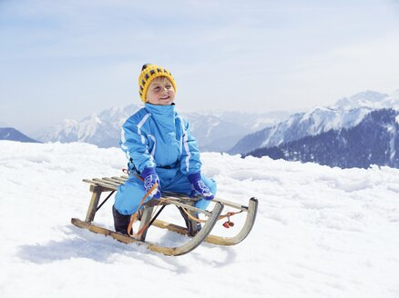 Germany, Tegernsee, Wallberg, smiling little boy sitting on sledge - EDF000133