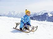 Germany, Tegernsee, Wallberg, smiling little boy sitting on sledge - EDF000134
