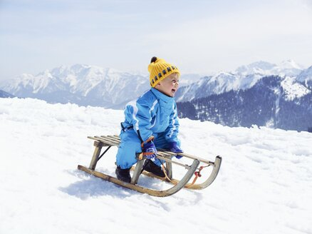 Germany, Tegernsee, Wallberg, smiling little boy sitting on sledge - EDF000134