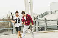 Two friends walking with skateboards and cell phone - UUF003666