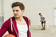 Two young men with skateboard and basketball on parking level - UUF003686