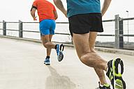 Two young men jogging on bridge - UUF003704