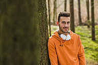 Smiling young man with headphones in forest - UUF003722