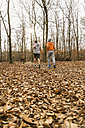 Two young men jogging in forest - UUF003732