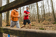 Two young men jogging in forest - UUF003738
