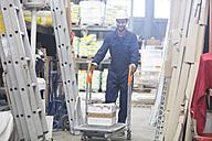 Warehouseman in storehouse pushing cart - SGF001406