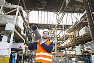 Warehouseman in storehouse carrying pipe - SGF001423