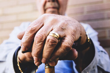 Close-up of old man's hands resting on a cane - GEMF000143