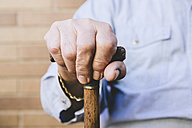 Close-up of old man's hands resting on a cane - GEMF000146