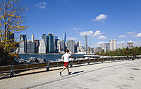 USA, New York, Brooklyn Bridge Park, jogger on a path beside the East River with the Lower Manhattan skyscraper skyline beyond - PS000668