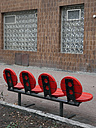 Germany, Berlin, row of red seats in front of facade with glass bricks - JMF000329