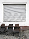 Germany, three old chairs in front of facade with closed roller shutter - JMF000331