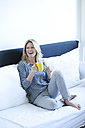Relaxed woman sitting on couch with cup of coffee - MAEF009960