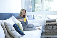 Relaxed woman sitting on couch with cup of coffee - MAEF009963