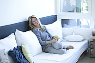 Relaxed woman sitting on couch with cup of coffee - MAEF009974