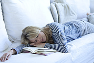 Woman lying on couch with a book sleeping - MAEF009980