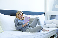 Woman sitting on couch reading a book - MAEF009987