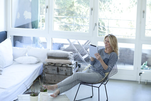 Smiling blond woman using digital tablet at home - MAEF009995