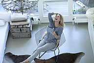 Laughing blond woman with digital tablet at living room - MAEF009997