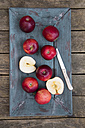 Red apples and knife on dark wood - SARF001583