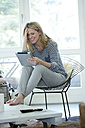 Smiling blond woman using digital tablet at home - MAEF010063