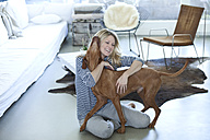 Woman playing with her dog at home - MAEF010006