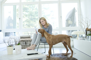 Woman with her dog and digital tablet at home - MAEF010012