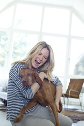 Woman playing with her dog at home - MAEF010015