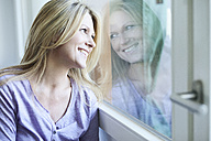 Blond woman looking through window - MAEF010036