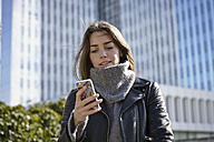 Germany, Dusseldorf, Young woman holding smart phone - RHF000658