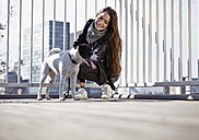 Germany, Dusseldorf, Young woman walking her dog - RHF000670