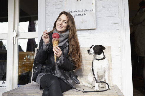 Germany, Dusseldorf, Young woman with dog eating icecream - RHF000679
