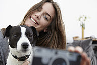 Young woman taking selfie with dog - RHF000719
