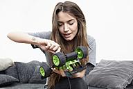 Young woman repairing toy car - RHF000724