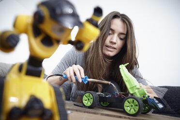 Young woman repairing toy car - RHF000727